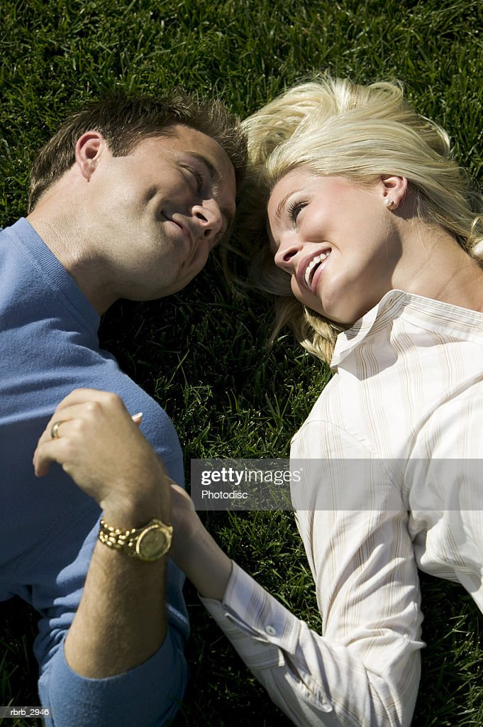 High angle view of a young couple lying on a lawn looking at each other : Foto de stock