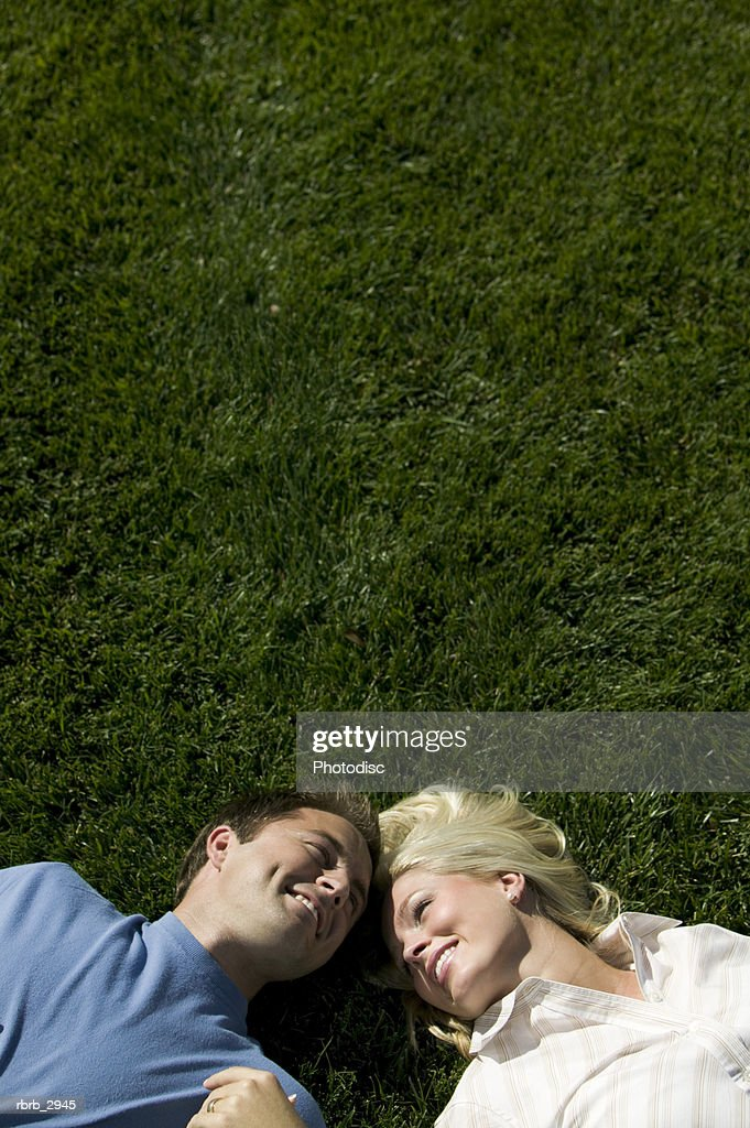 High angle view of a young couple lying on a lawn : Foto de stock
