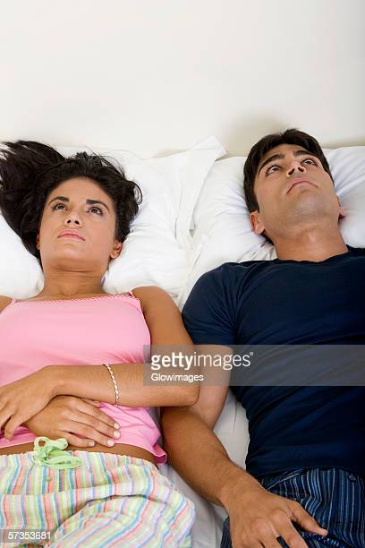 High angle view of a young couple lying on the bed looking up