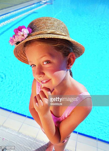high angle view of a young girl smiling and standing outside a pool