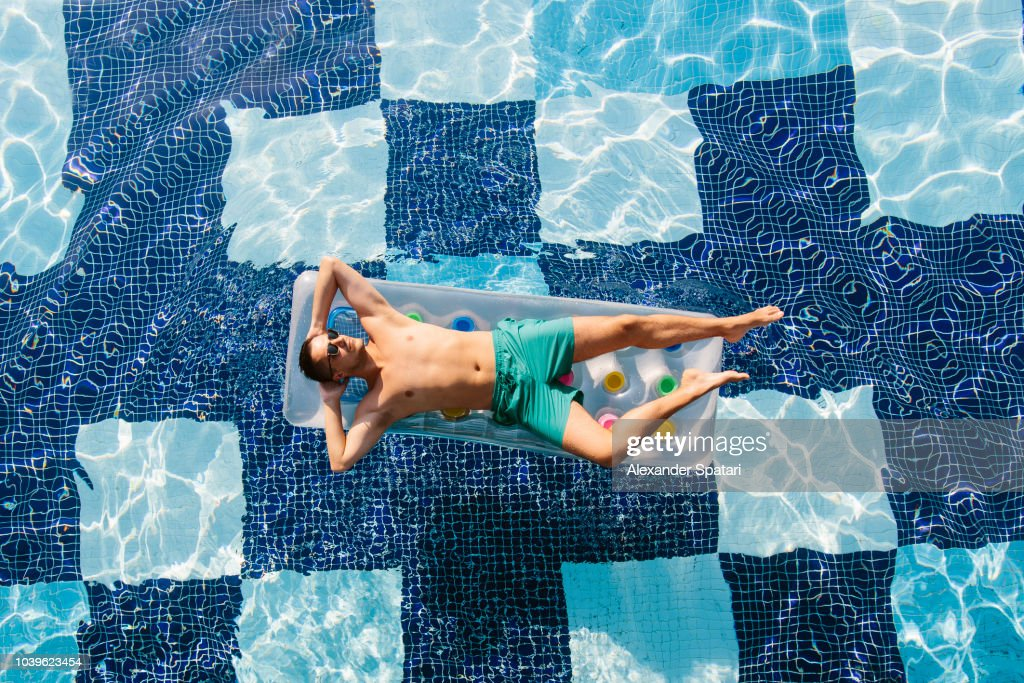 High angle view of a young man in sunglasses sunbathing in swimming pool on inflatable pool raft : Foto de stock