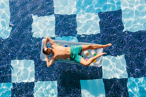 High angle view of a young man in sunglasses sunbathing in swimming pool on inflatable pool raft - gettyimageskorea