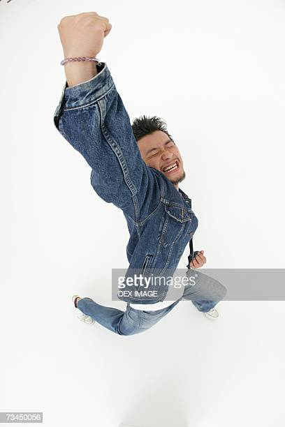 High angle view of a young man jumping with his eyes closed
