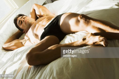 High Angle View Of A Young Man Sleeping On The Bed High