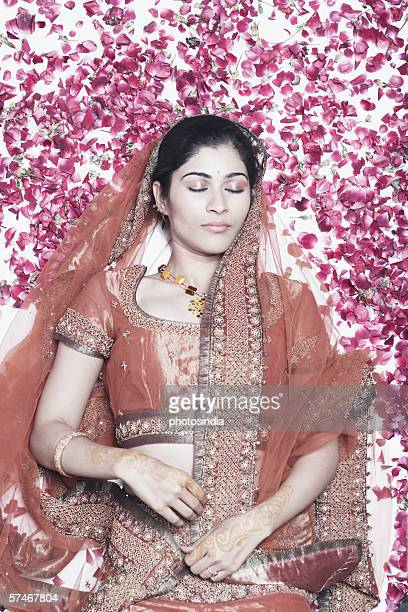 High angle view of a young woman lying on rose petals