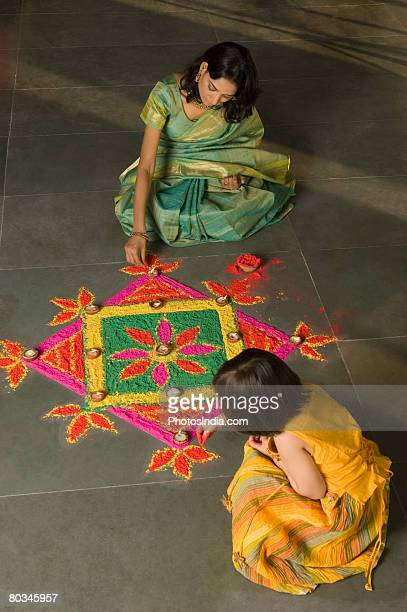 High angle view of a young woman making rangoli with her daughter