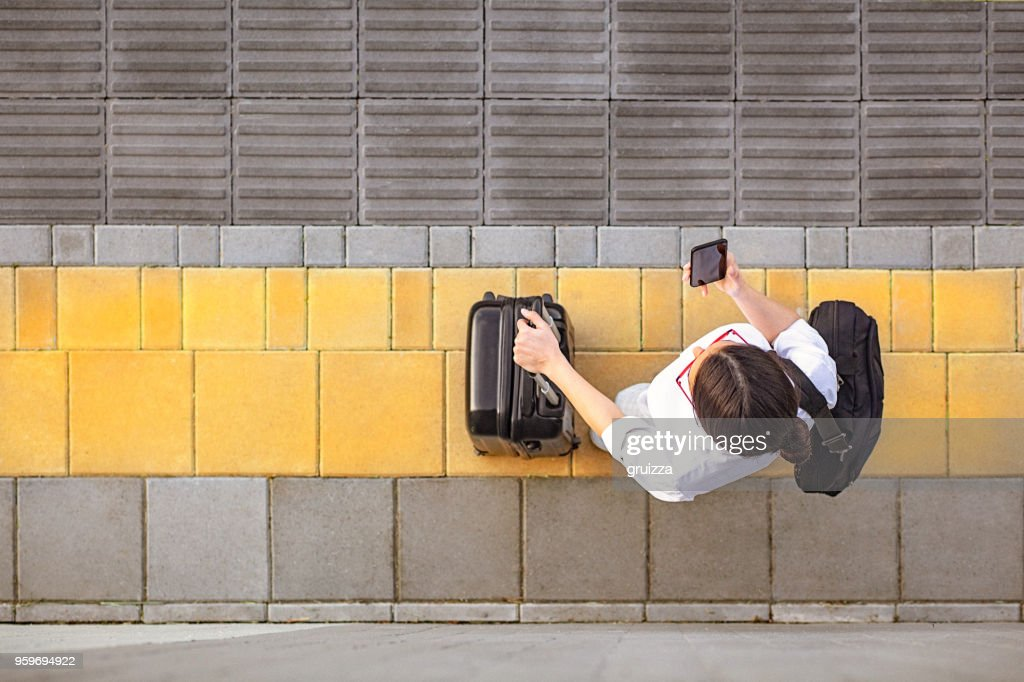 Erhöhte Ansicht einer jungen Frau, die mit ihrem Smartphone : Stock-Foto