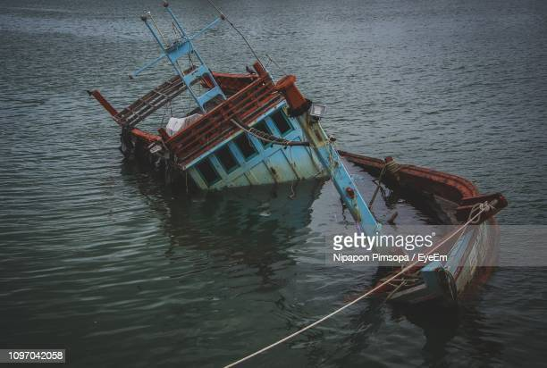 high angle view of abandoned boat in sea - sinking stock pictures, royalty-free photos & images