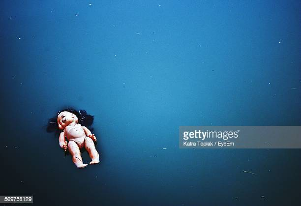 High Angle View Of Abandoned Doll On Blue River