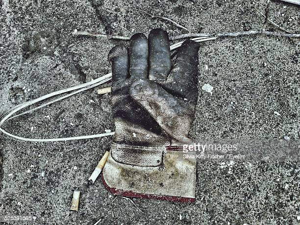 high angle view of abandoned glove on footpath - work glove stock pictures, royalty-free photos & images