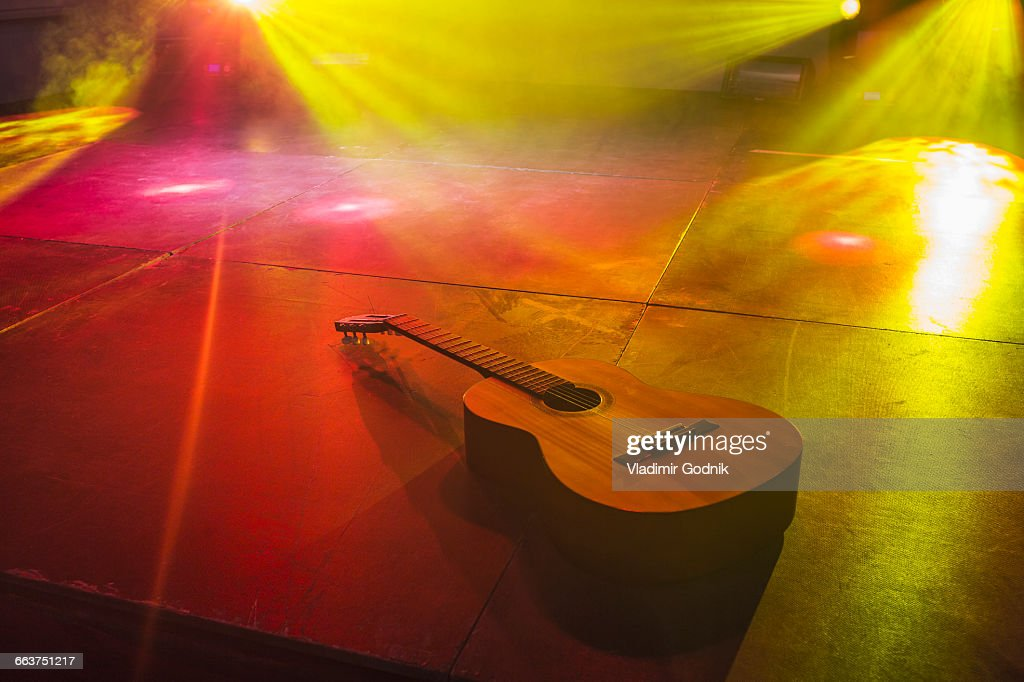 High Angle View Of Acoustic Guitar On Illuminated Stage Stock Photo