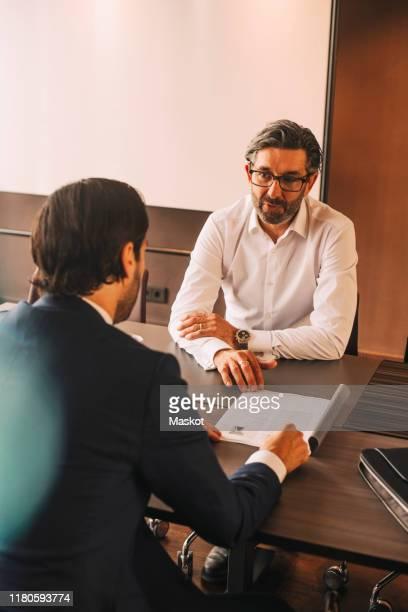 high angle view of advisor explaining document to businessman in meeting at law office - vestuário de trabalho formal imagens e fotografias de stock