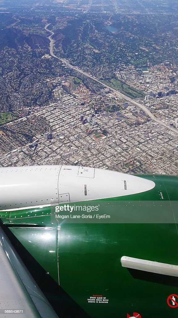 High Angle View Of Airplane Flying Above Cityscape : Stock Photo