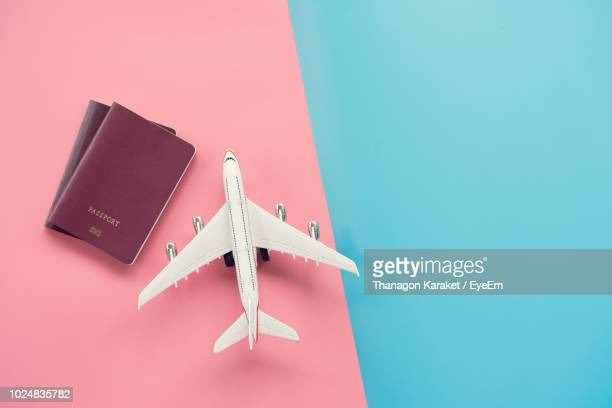 high angle view of airplane model with passports on colored background - passeport photos et images de collection