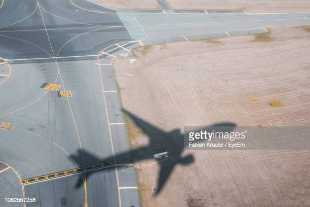 high angle view of airplane on airport runway - ombra in primo piano foto e immagini stock