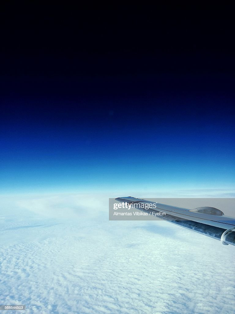 High Angle View Of Airplane Wing Flying Over Snow Mountain Against Sky : Stock Photo