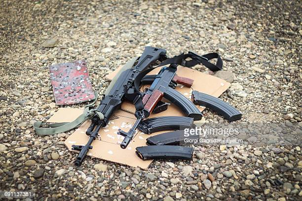 High Angle View Of Ak-47 Guns And Cartridges On Stones