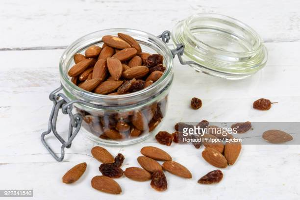 High Angle View Of Almonds And Raisins In Jar On Table