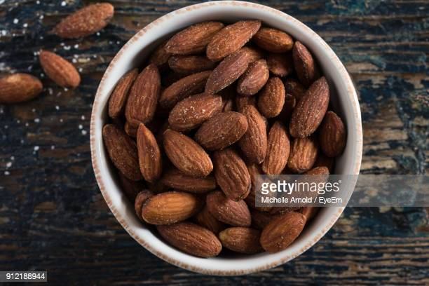 high angle view of almonds in bowl on table - salted stock pictures, royalty-free photos & images