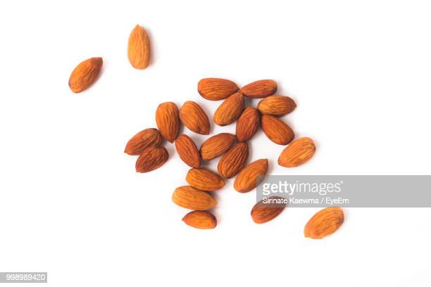 high angle view of almonds on white background - nut food stock pictures, royalty-free photos & images