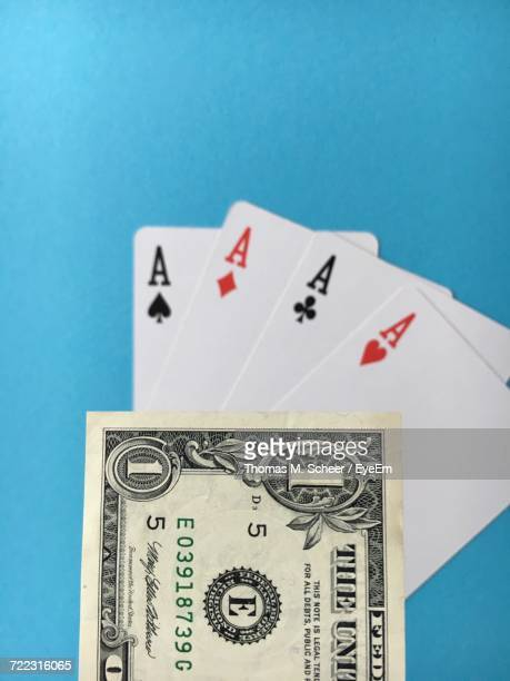 High Angle View Of American One Dollar Bill With Ace Cards On Table