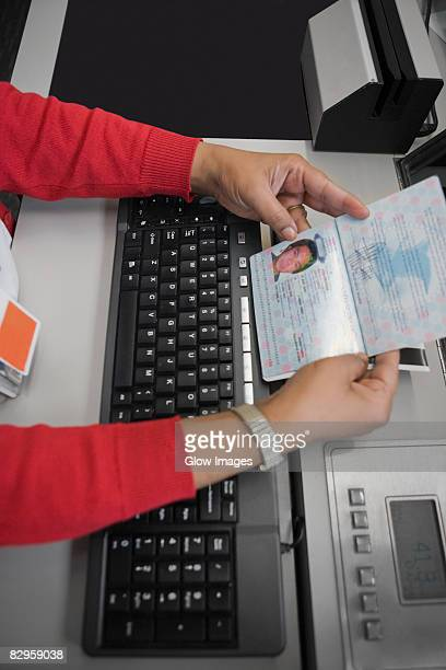 High angle view of an airline check-in attendant checking a passport