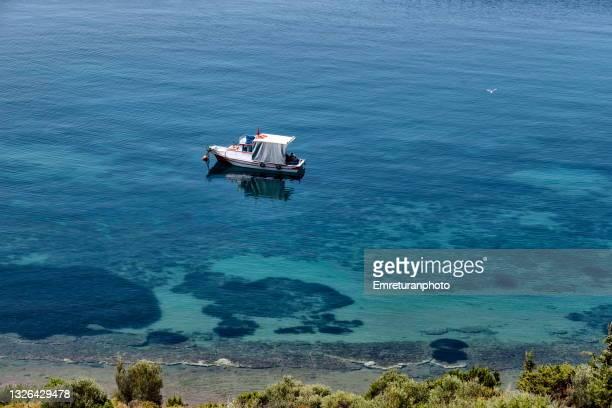 high angle view of an anchored boat along the coast in karaburun. - emreturanphoto fotografías e imágenes de stock