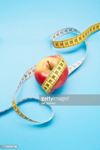 high angle view of an apple and tape measure on blue background - センチメートル ストックフォトと画像
