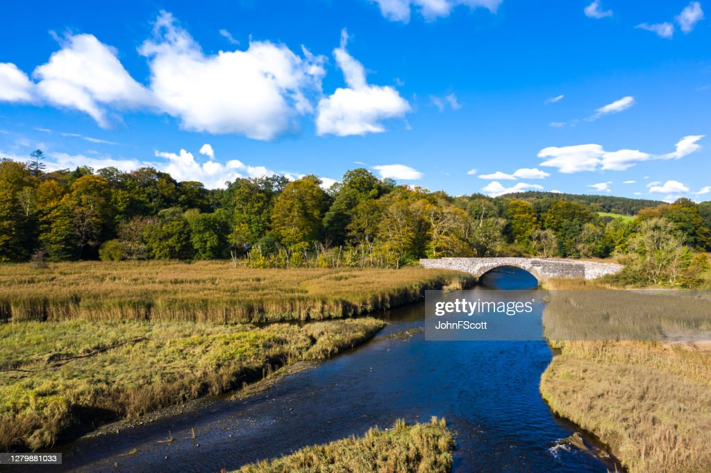 High angle view of an old stone bridge crossing a small river in Dumfries and Galloway south west Scotland : Stock Photo