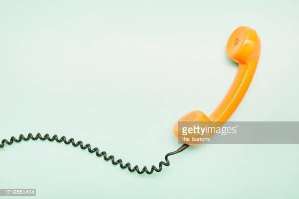 high angle view of an orange old-fashioned telephone receiver on turquoise background - einzelner gegenstand stock-fotos und bilder