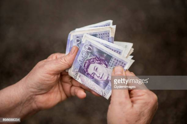 high angle view of an unrecognizable person holding group of twenty (20) pound notes - british pound sterling note stock pictures, royalty-free photos & images