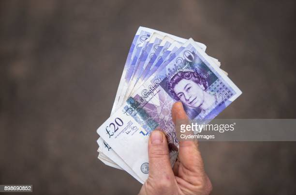high angle view of an unrecognizable person holding group of twenty (20) pound notes - twenty pound note stock photos and pictures