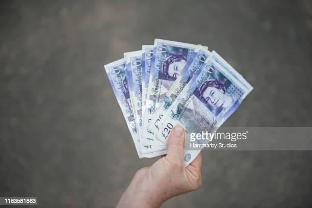 high angle view van een onherkenbaar senior volwassen holding groep van britse valuta pond bankbiljetten - twenty pound note stockfoto's en -beelden