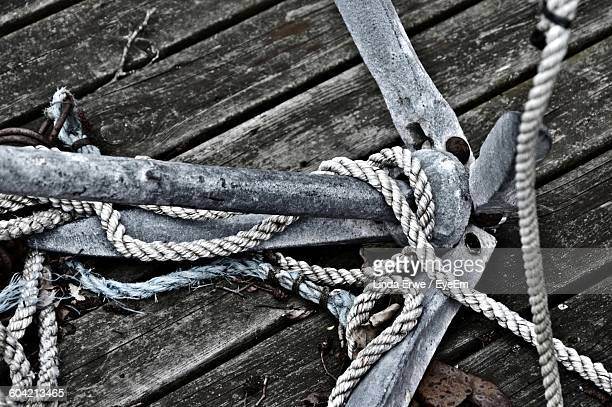 High Angle View Of Anchor And Rope On Wood