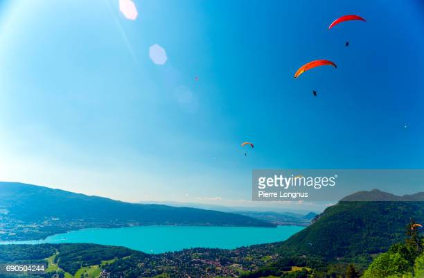 high angle view of annecy lake with the village of talloires at the bottom - paragliders flying above - the city of annecy is visible in the backdrop - lake annecy stock photos and pictures