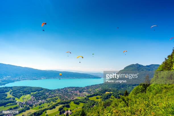 high angle view of annecy lake with the village of talloires with paragliders flying above - the city of annecy is visible in the backdrop - lake annecy stock photos and pictures