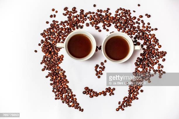 High Angle View Of Anthropomorphic Face Made With Coffee Cups And Roasted Beans On White Background