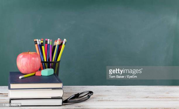 high angle view of apple with book and school supplies on table against blackboard - blackboard stock pictures, royalty-free photos & images