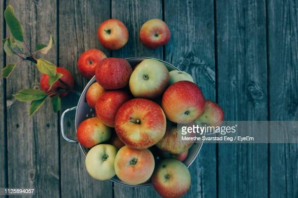 high angle view of apples in bucket on wooden table - orchard stock pictures, royalty-free photos & images
