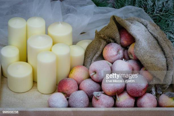 High Angle View Of Apples In Sack With Candles On Table During Winter