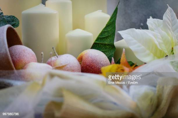 High Angle View Of Apples With Candles And Flowers On Table During Winter