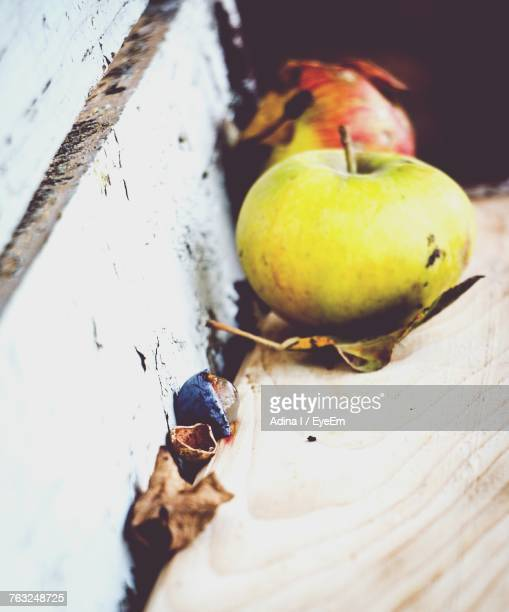 High Angle View Of Apples With Dry Leaves On Wooden Table