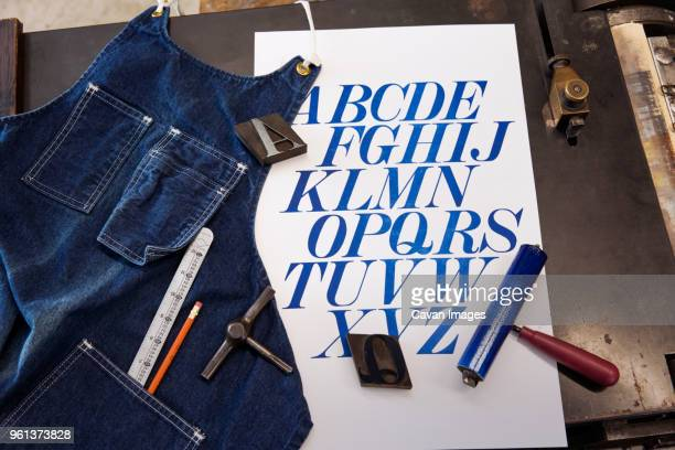 High angle view of apron by poster and tools on table
