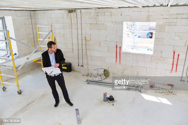 Director of business development stock photos and pictures getty high angle view of architect with blueprint standing in incomplete building malvernweather Images