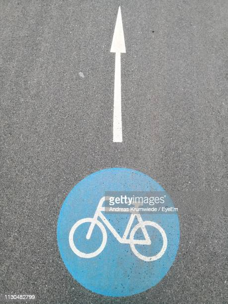 High Angle View Of Arrow And Bicycle Signs On Road