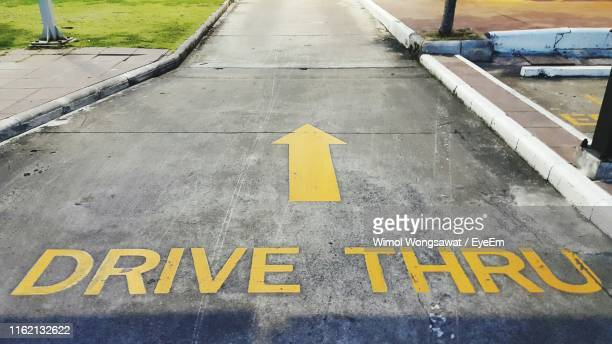 high angle view of arrow sign and text on road - wimol wongsawat stock photos and pictures
