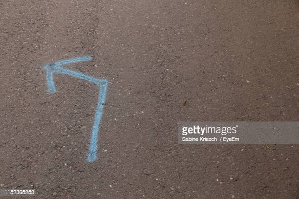 high angle view of arrow sign on road - sabine kriesch stock-fotos und bilder