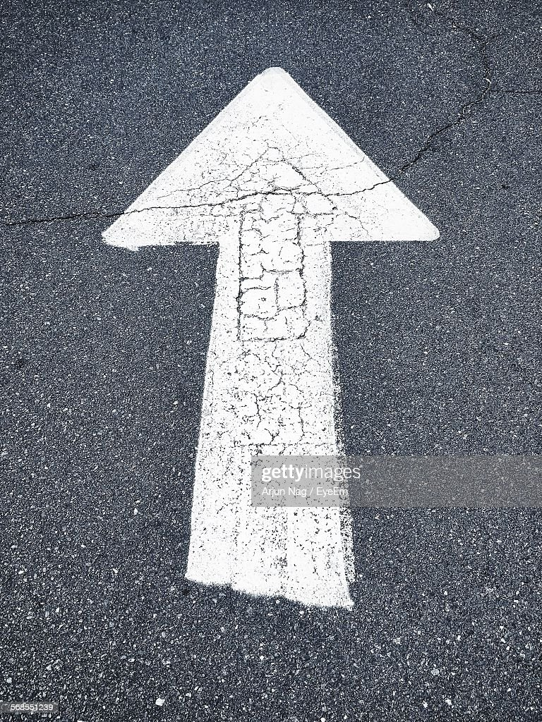 High Angle View Of Arrow Sign On Road : Stock Photo