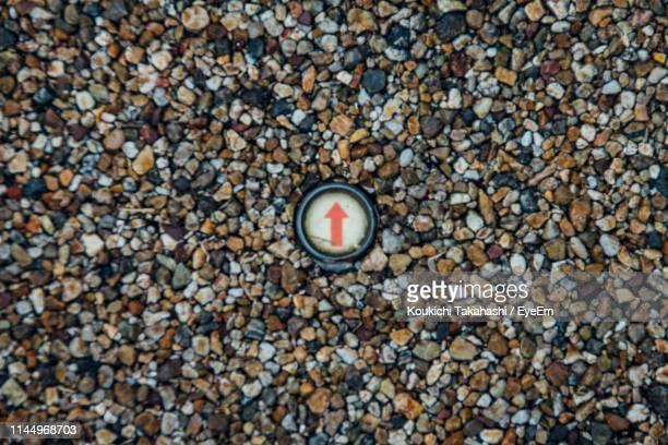 High Angle View Of Arrow Symbol On Pebbles At Beach