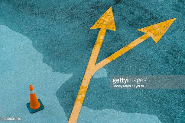 high angle view of arrow symbol on road - arrow stock photos and pictures
